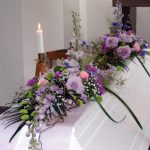 kistdekoration begravning lila blommor brudslöja rosa blommor
