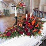 kistdekoration röda rosor orangea blommor granbarr fiskespö svampar