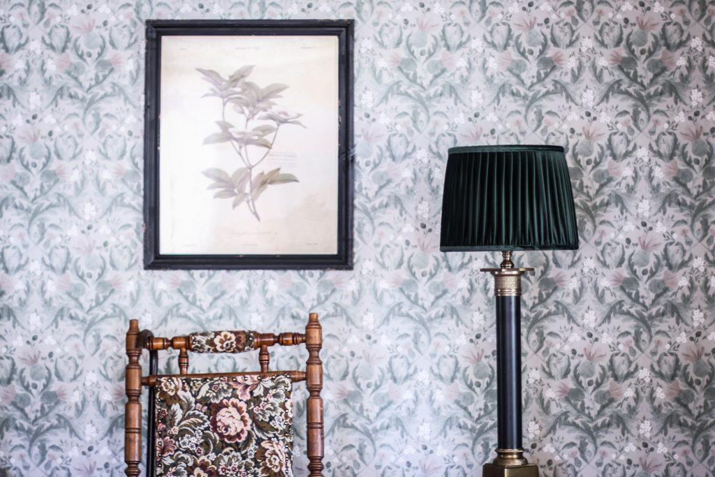 grön lampskärm tavla tapet brun stol med blommönster
