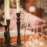 provrör med blommor i som står bredvid ljusstakar